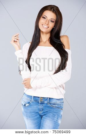 Trendy fashionable young woman with a lovely figure and warm friendly smile standing looking at the camera in jeans and an off the shoulder top
