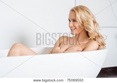 Laughing attractive blond with long curly hair woman posing nude in a bath concealing her breasts with her hands