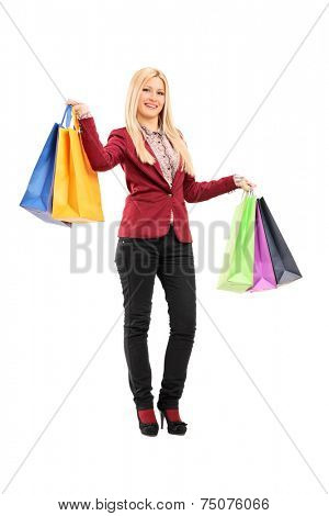 Full length portrait of an elegant woman holding shopping bags isolated on white background