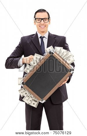 Vertical shot of a delighted businessman holding a briefcase full of money isolated on white background
