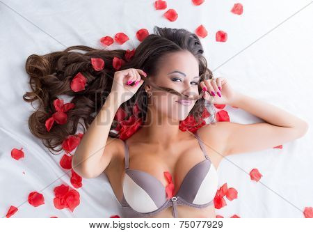 Portrait of funny lingerie model posing in bed