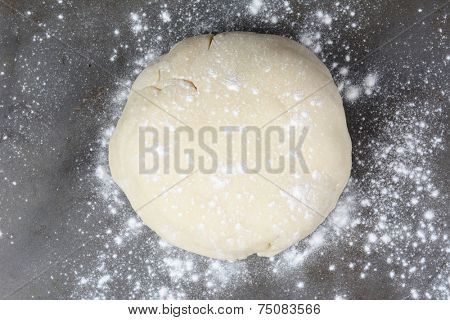 Overhead shot of a ball of dough on a baking sheet sprinkled with flour. Horizontal format.