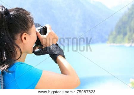 woman tourist/photographe r taking photo with digital camera in jiuzhaigou national park,china