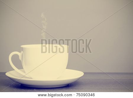 White cup and saucer on wooden table