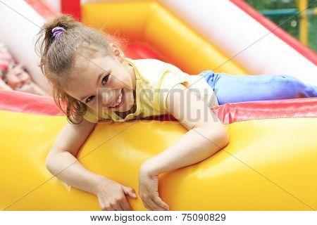 Joyful little girl playing on trampoline.