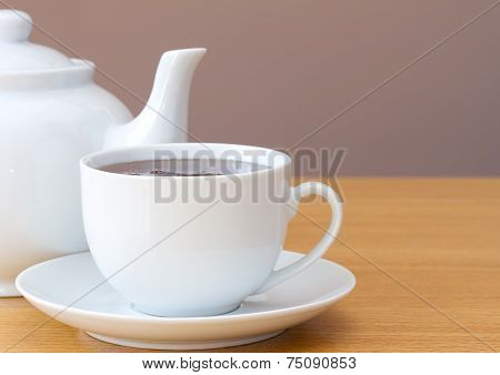 Cup of tea with a white teapot on a table