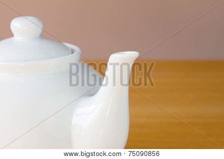 Close up white teapot on a wooden table