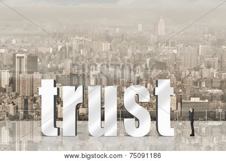 Concept of trust, belief, credit etc with 3d text under sky in the modern city and one Asian business man looking it.