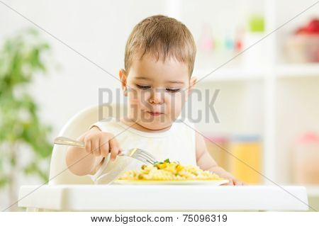 one year old child boy in a highchair for feeding with a fork an