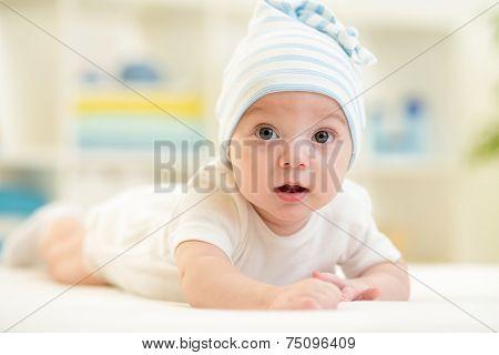 baby boy lying on bed in nursery