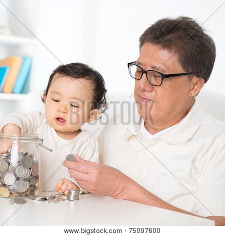 Asian family saving coins indoor, grandpa and grandchild living lifestyle at home.