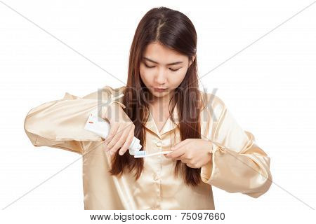 Asian Woman In Pajamas With Toothbrush And Toothpaste