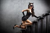 stock photo of catsuit  - sexy woman in cat suit lying on stairs at backyard of building - JPG