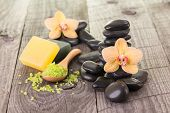 stock photo of yellow orchid  - Yellow Moth orchids, bath salt, soaps and black stones on weathered deck