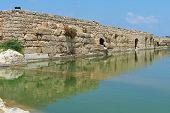 Photo of ancient wall reflecting in the pond in nahal taninim archeological park in israel.