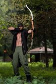foto of longbow  - Beard Man With A Bow And Arrows In The Woods - JPG
