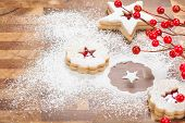 foto of linzer  - Christmas Linzer Cookies with powdered sugar on a wooden background - JPG