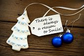image of saying  - Christmas Tree Cookie And Two Blue Christmas Balls With White Label With Life Quote Saying There Is Always A Reason To Smile On Wooden Background - JPG
