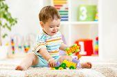 stock photo of kindergarten  - kid boy playing with building blocks at home or kindergarten - JPG