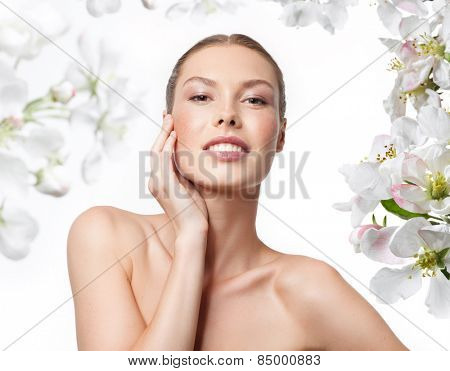 portrait of attractive  caucasian smiling woman blond isolated on white studio shot  toothy smile face skin care hand head and shoulders looking at camera spring flowers