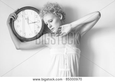Tender young girl with curly hair and a big clock in his hands. Black and white photography in bright colours.