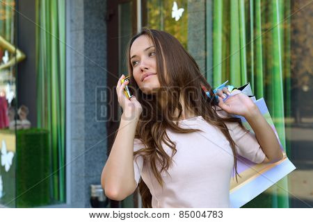 Beautiful young fashion woman with shopping bags near shop window calling smart phone
