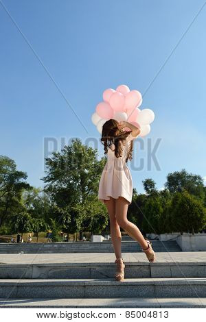 Fashion girl with air balloons steps on stairs