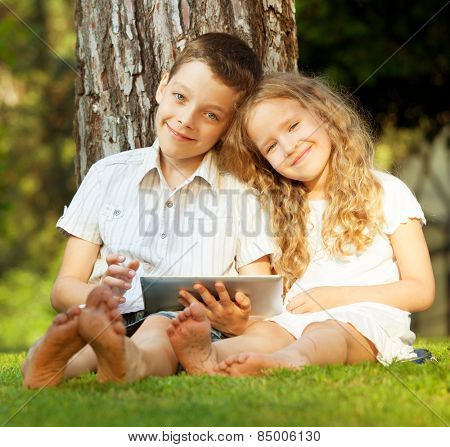 Children with tablet computer outdoors. Girl and boy playing at pc