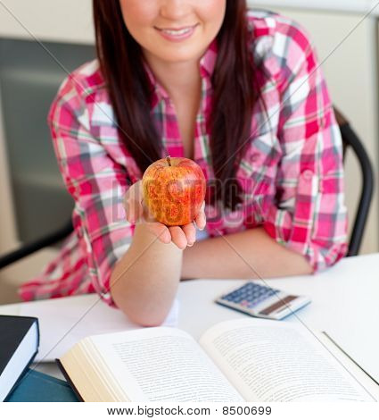 Close-up Of A Delighted Caucasian Woman Holding An Apple Sitting In The Kitchen