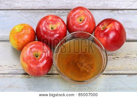 Fresh apples and a bowl of raw and unfiltered organic apple cider vinegar with mother enzymes