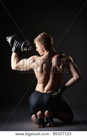 Athlete man doing exercises with dumbbells. Bodybuilding. Muscles of the arms and back. Studio shot over black background.