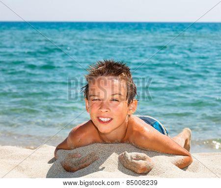 Happy boy enjoying summer day on a beach