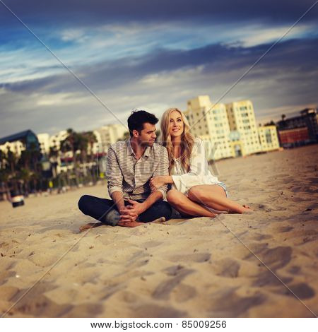 cute couple on beach cuddling while watching sunset
