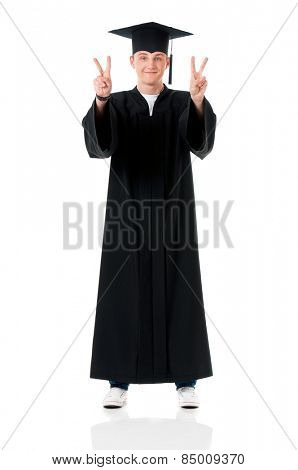 Handsome graduate guy student in mantle showing victory signs, isolated on white background