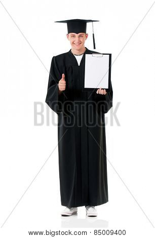 Graduate guy student in mantle showing blank placard board and thumb up, isolated on white background