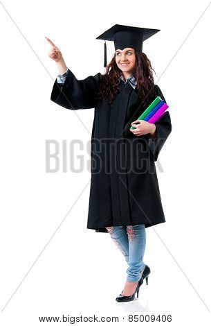 Young graduate girl student in mantle with books showing something, isolated on white background