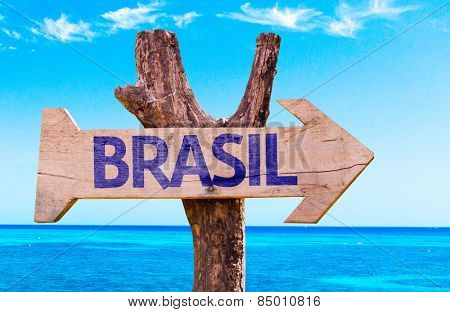 Brazil (in Portuguese) wooden sign with a beach on background