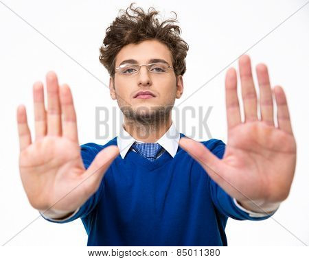 Confident business man showing stop gesture over white background
