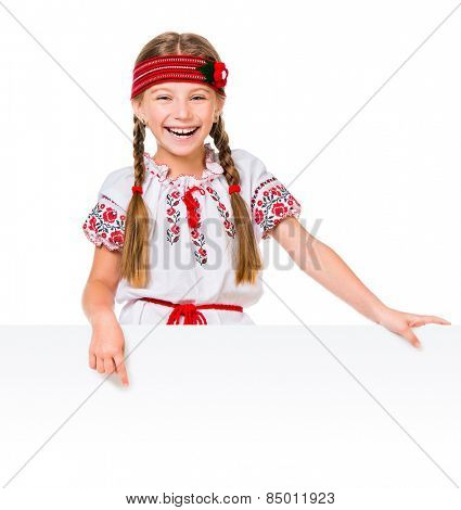 happy little girl in the Ukrainian national costume behind white board with space for text