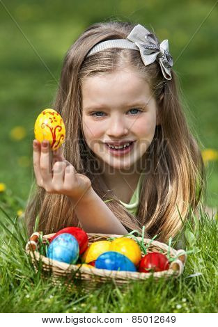 Happy child find easter egg outdoor. Long blond hair.