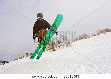 Jumping skier at jump inhigh mountains at sunny day