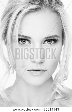 Black and white hi-key portrait of young beautiful blonde girl with extended eyelashes