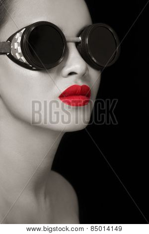 Black and white portrait of young beautiful girl in vintage steampunk glasses