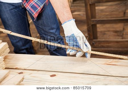 Midsection of male construction worker measuring wooden plank with tape