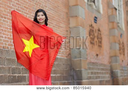Happy patriotic young Vietnamese woman with a lovely warm smile holding up the national flag in her arms as she stands against brick buildings in an urban street, with copyspace