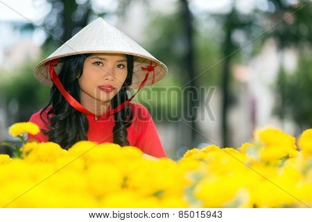 Attractive young Vietnamese woman in a traditional hat looking at the camera with a serious expression over a display of colorful vivid yellow flowers in a park