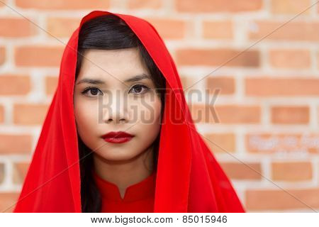 Serene elegant young Vietnamese woman in a traditional red outfit with a scarf over her hair looking directly at the camera with a serious expression against a brick wall with copyspace