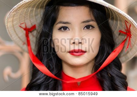 Pretty young Vietnamese woman in a red top with matching lipstick wearing straw hat, close up face portrait looking into the camera