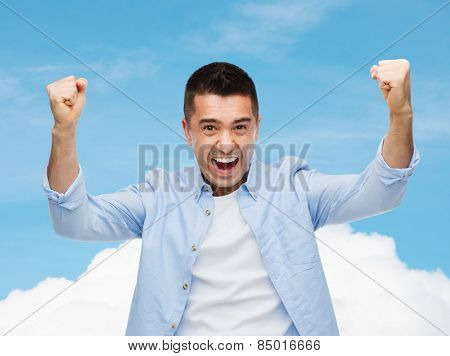 happiness, gesture, emotions and people concept - happy laughing man with raised hands over blue sky and cloud background