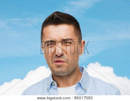 emotions, facial expression and people concept - man wrying of unpleasant smell over blue sky and cloud background